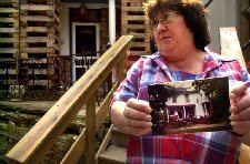 Diane Brendel stands in front of her Spraggs, (Green County), PA home showing a photograph of her home before Consol Energy longwall mined under the property two years ago. The Brendels' home, which they purchased in 1970 and restored, is on the National Register of Historic Places and is considered to be the finest example of Spanish revival architecture in southwestern PA. Photo by Pam Panchak. Courtesy Pittsburgh Post-Gazette.